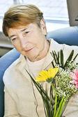 Sad elderly woman with flowers — Stock Photo