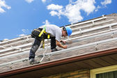 Man working on roof installing rails for solar panels — Stok fotoğraf