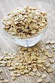 Bowl of raw rolled oats — Stock Photo