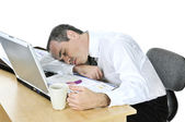 Businessman asleep at his desk on white background — Stock Photo