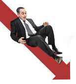 Businessman sliding down red arrow — Stock Photo