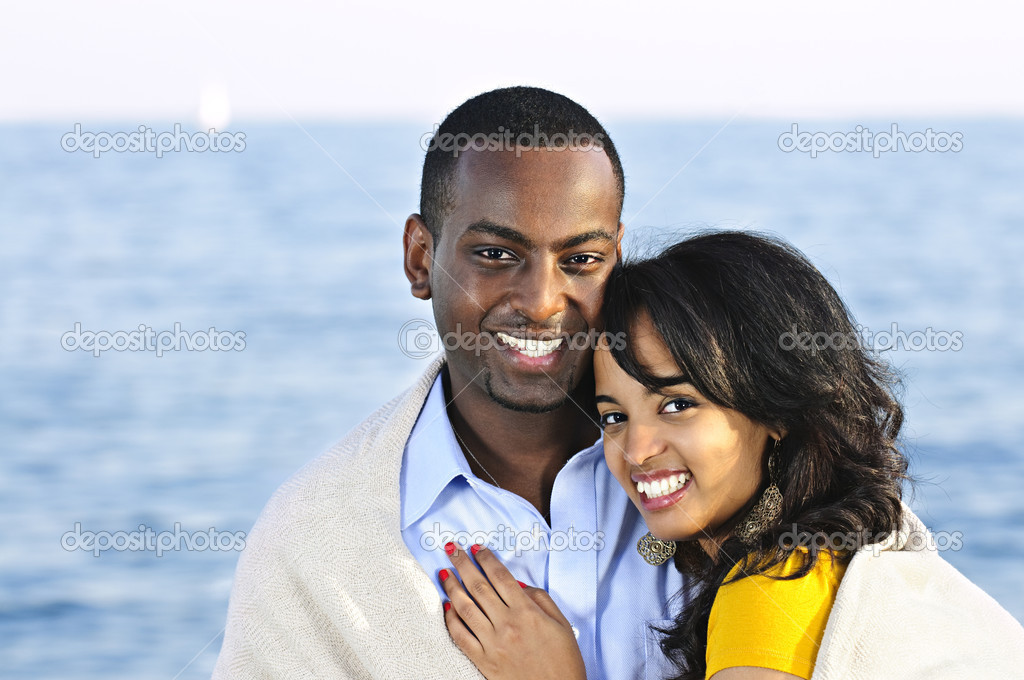 Young romantic sharing a blanket by the ocean — Stock Photo #4718454