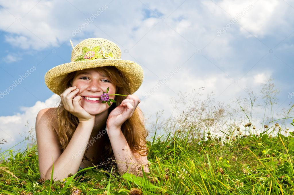 Young teenage girl laying in summer meadow resting chin on hand holding flower  Stock Photo #4718884