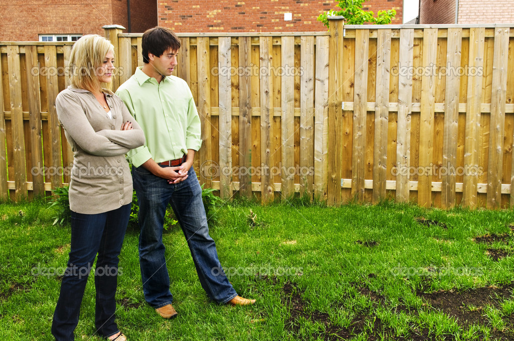 Young couple worried about growing lawn in backyard of new home — Stock Photo #4719115