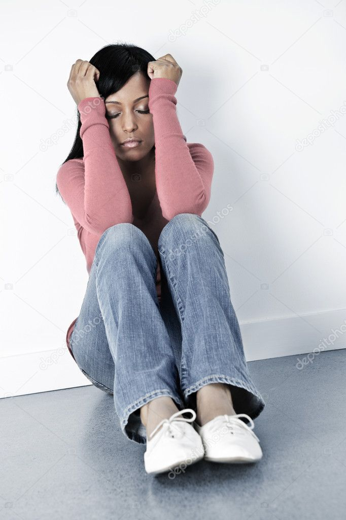 Depressed black woman sitting against wall on floor with eyes closed  Stock Photo #4719228