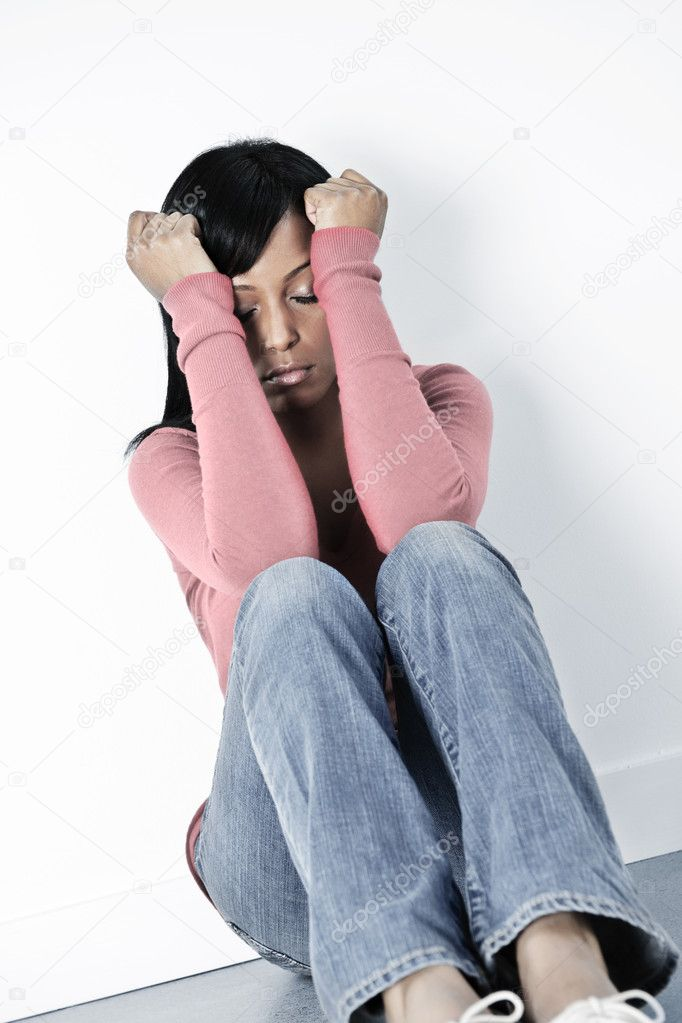 Depressed black woman sitting against wall on floor with eyes closed — Stock Photo #4719229