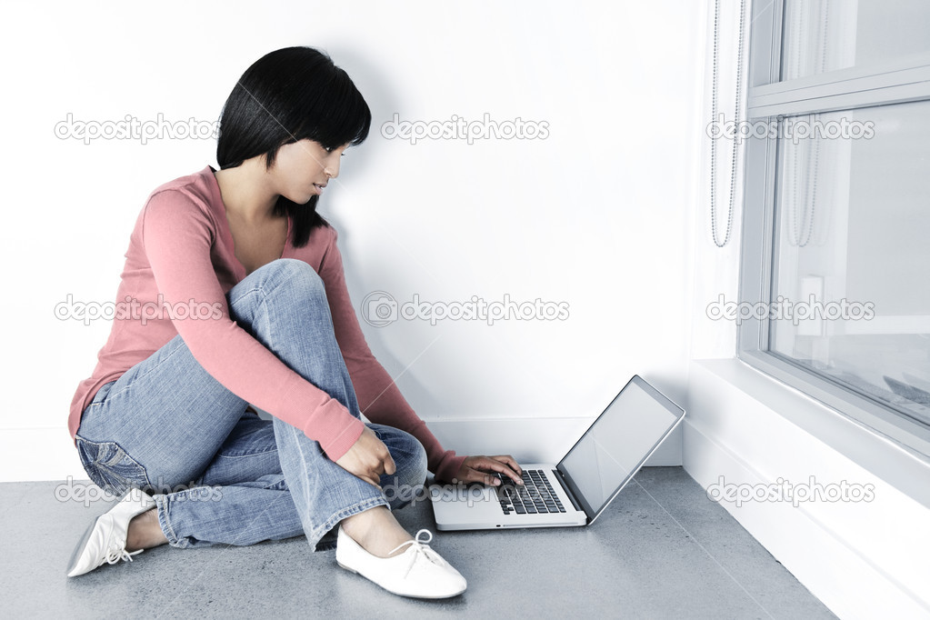 Young black woman with computer sitting on floor looking at laptop — Stock Photo #4719237