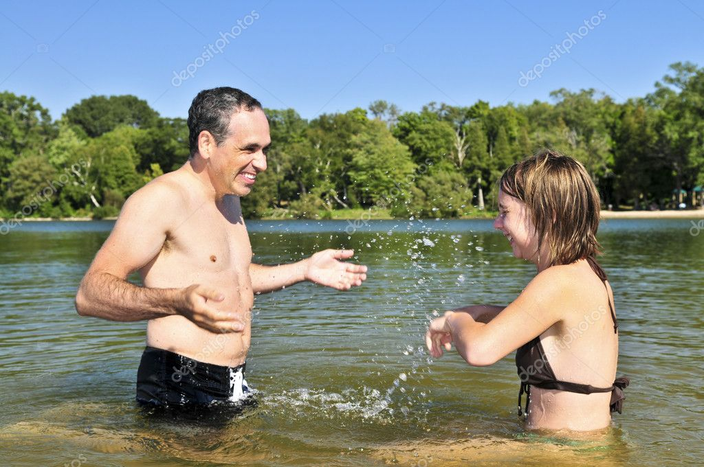 Father and daughter splashing in a lake  Stock Photo #4719300