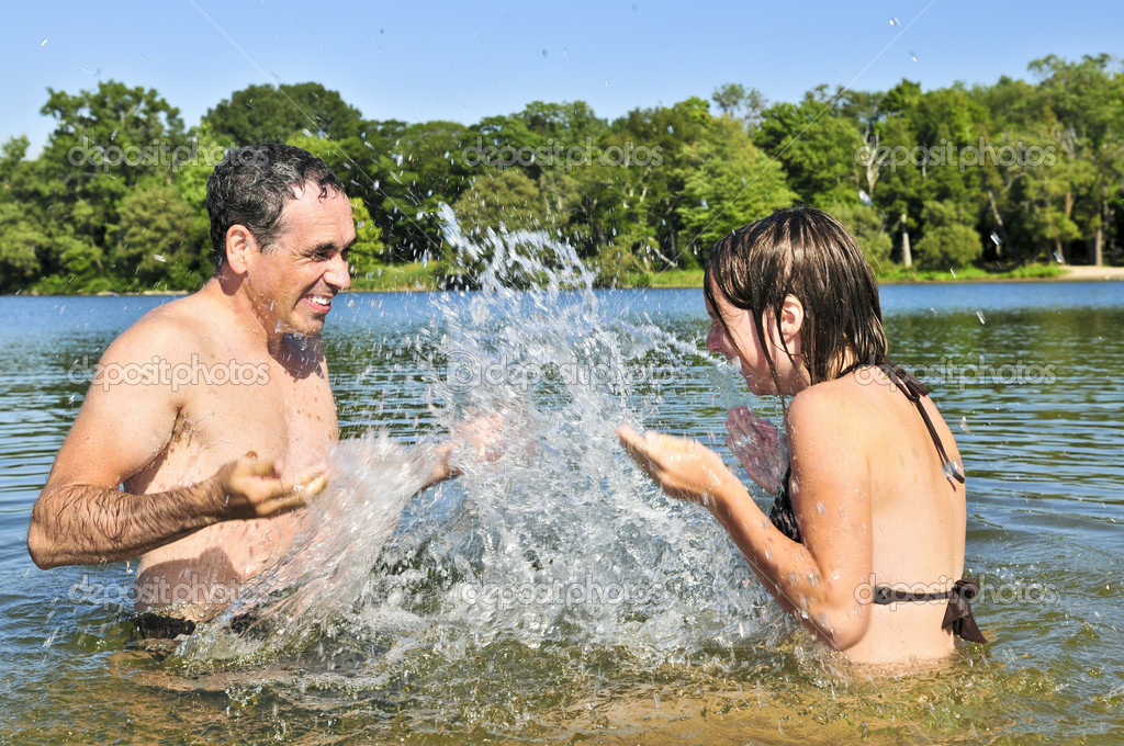 Father and daughter splashing in a lake — Stock Photo #4719301