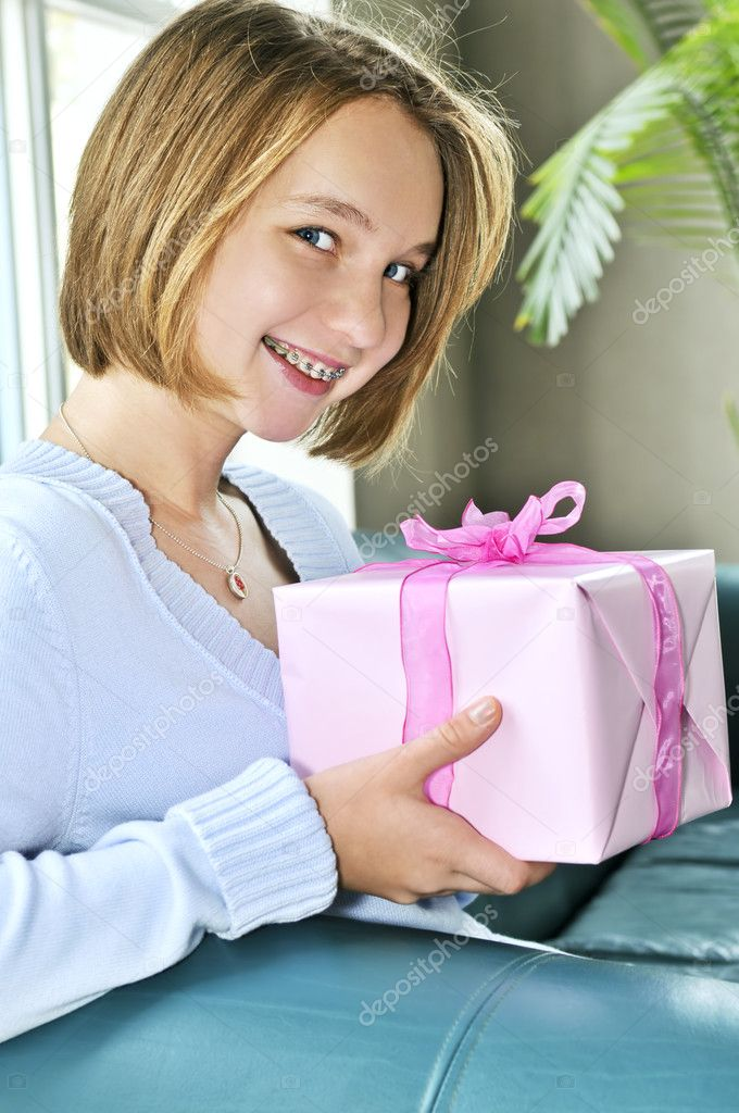 Teenage girl with braces holding wrapped present and smiling — Stock Photo #4719319