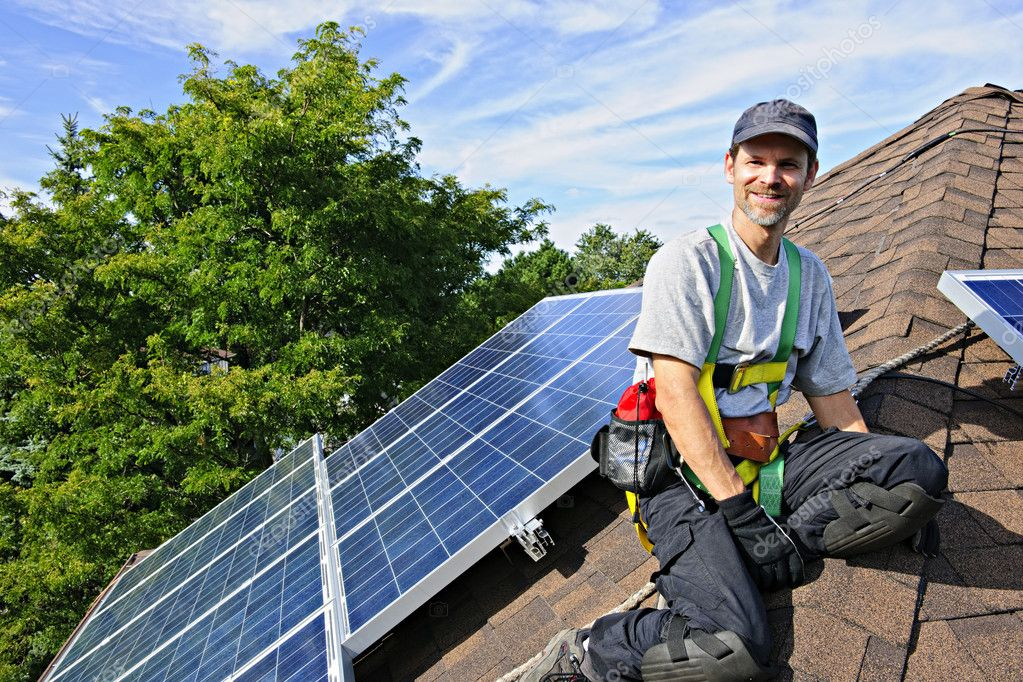 Man installing alternative energy photovoltaic solar panels on roof — Stock Photo #4719433