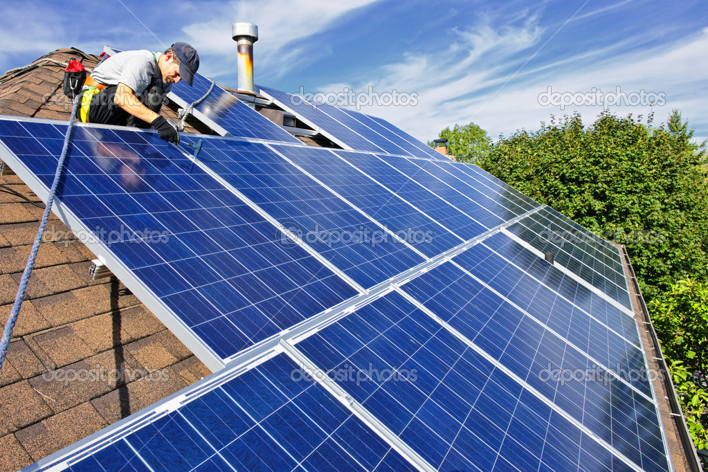 Man installing alternative energy photovoltaic solar panels on roof — Stok fotoğraf #4719434
