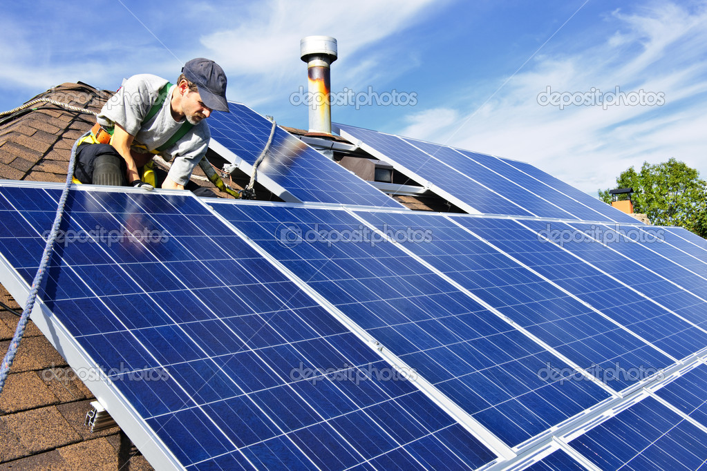 Man installing alternative energy photovoltaic solar panels on roof — Stock Photo #4719437