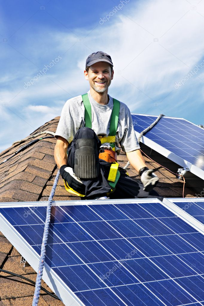 Man installing alternative energy photovoltaic solar panels on roof — Stock Photo #4719440