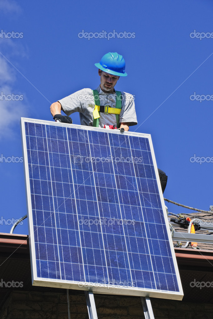 Man installing alternative energy photovoltaic solar panels on roof — Stock Photo #4719441