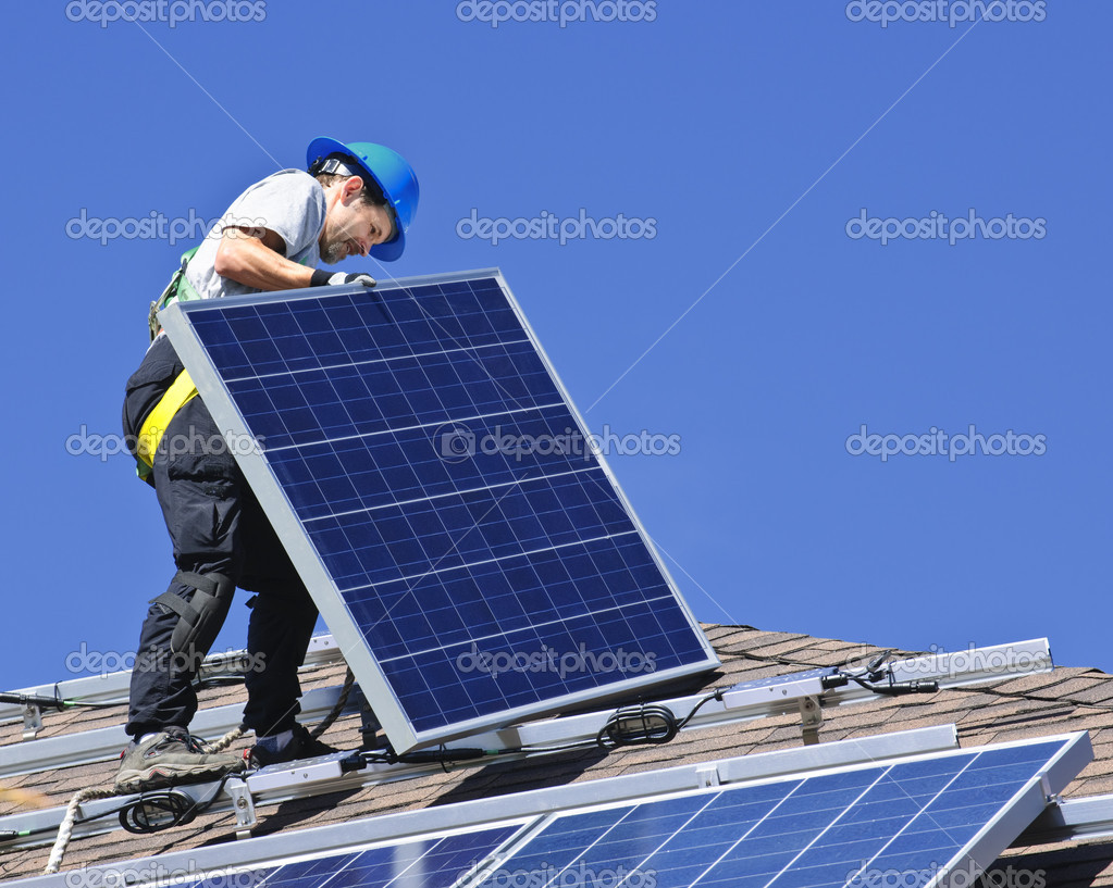 Man installing alternative energy photovoltaic solar panels on roof — Stock Photo #4719442