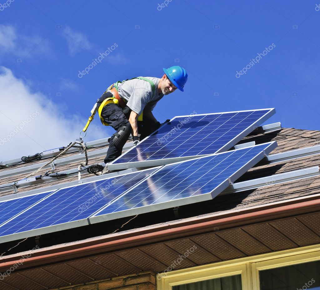 Man installing alternative energy photovoltaic solar panels on roof  Foto de Stock   #4719446