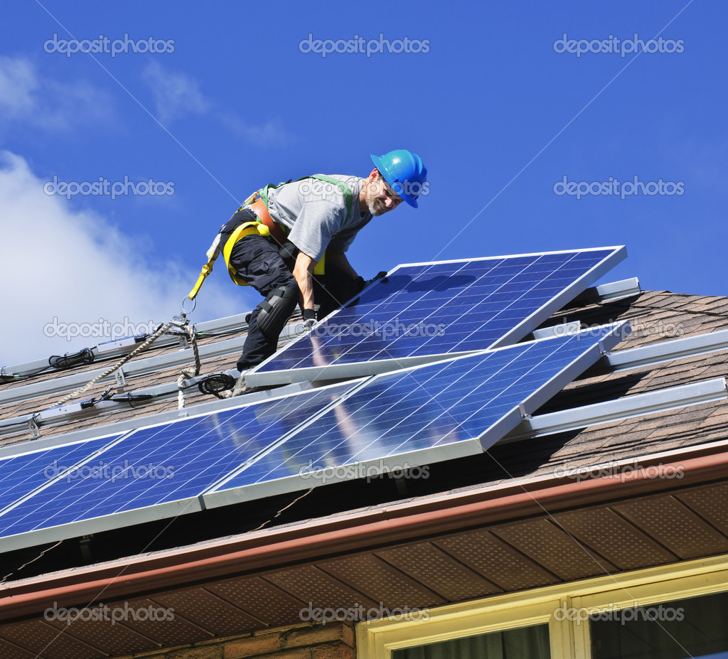 Man installing alternative energy photovoltaic solar panels on roof    #4719446