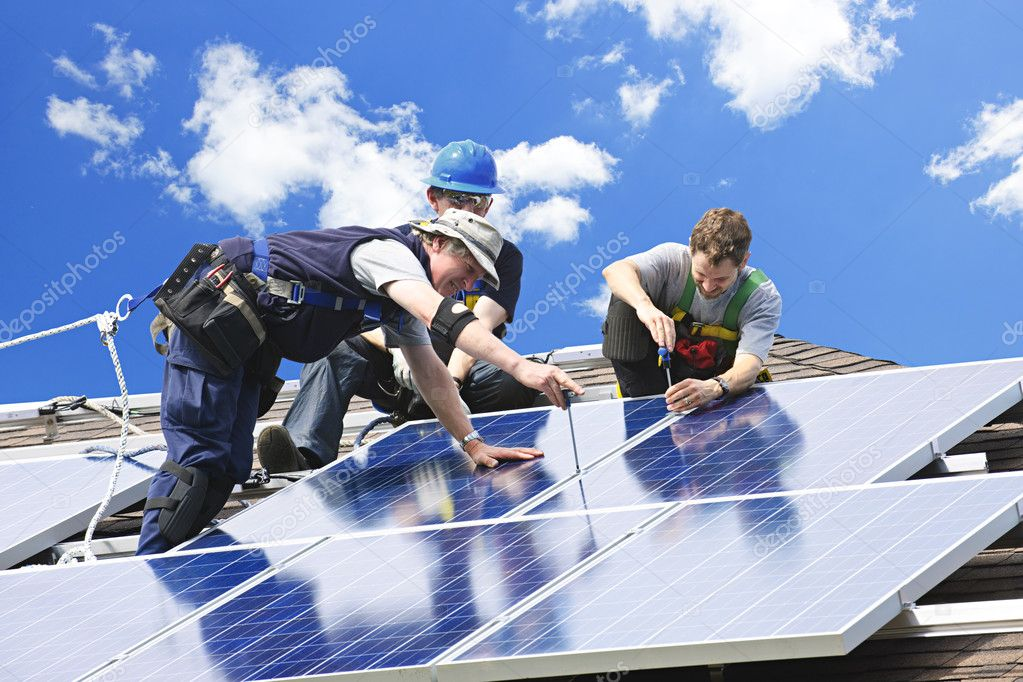 Workers installing alternative energy photovoltaic solar panels on roof  Stockfoto #4719457