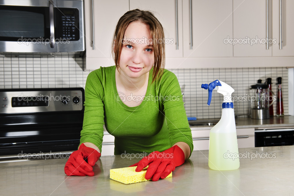 Young woman cleaning kitchen — Stock Photo © elenathewise ...