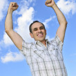 Happy man raising hands in victory — Stock Photo
