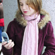 Teenage girl text messaging on cell phone - ストック写真