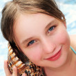 Young girl with seashell - Stock Photo