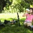 Teenage girl resting in a park with a bicycle — Stock Photo #4720187