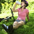 Teenage girl resting in a park with a bicycle - Stock Photo
