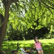 Teenage girl relaxing in a park with her bicycle — Stock Photo #4720209