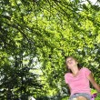 Teenage girl relaxing in a park with her bicycle — Stock Photo