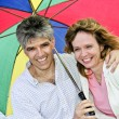 Happy mature couple with umbrella — Stock Photo