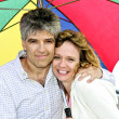 Happy mature couple with umbrella - Photo