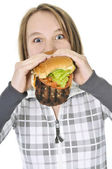 Teenage girl eating big hamburger — Stock Photo