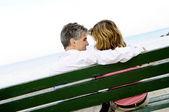Зрелые романтическая пара на скамейке — Стоковое фото