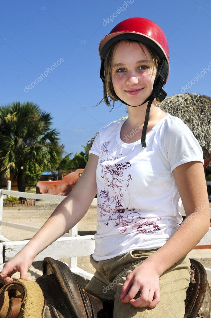 Young girl in a saddle wearing red helmet  Stock Photo #4720237