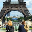 Tourists at Eiffel tower - Stock Photo