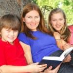 Family reading a book — Stock Photo #4826090