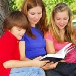 Family reading a book — Stock Photo