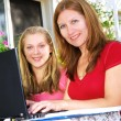 Mother and daughter with computer - Stock Photo
