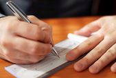 Man writing a check — Stockfoto