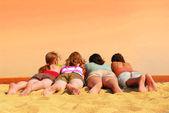 Four girls at orange sea — Stock Photo