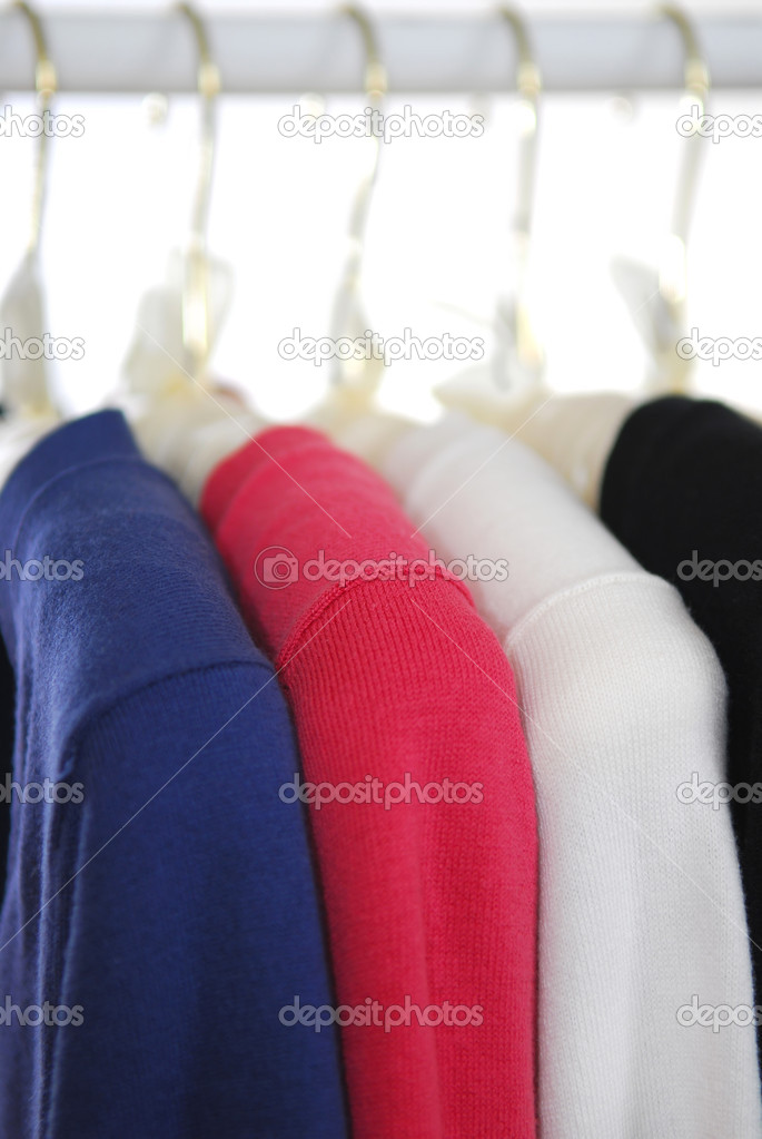 Colorful women's sweaters on a rack on padded hangers — Stock Photo #4824290