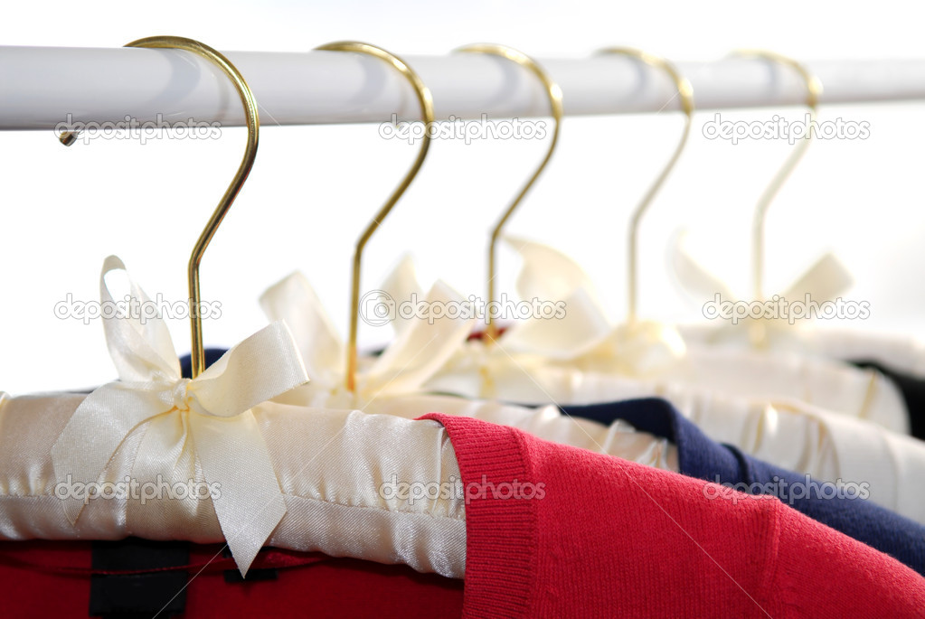 Colorful women's sweaters on a rack on padded hangers  Stock Photo #4824293