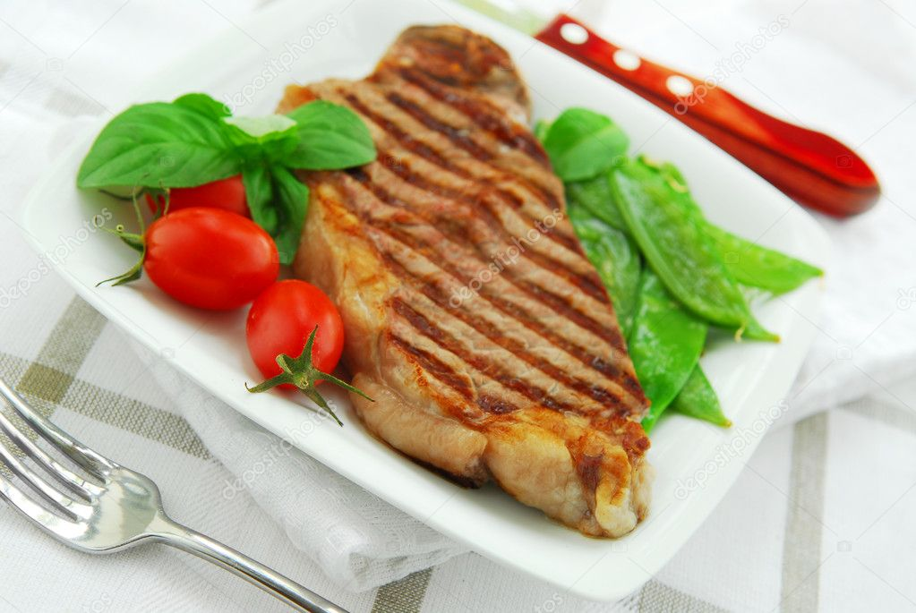 Grilled New York beef steak served on a plate with vegetables — Stock Photo #4825570