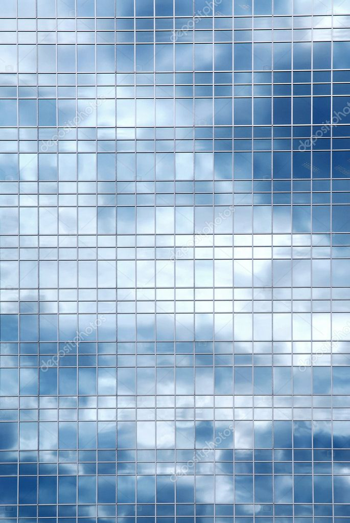 reflection of a cloudy sky in glass wall of an office building photo by elenathewise building an office
