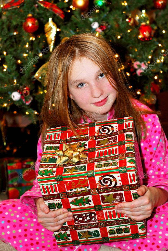Young girl holding a big Christmas present sitting under a Christmas tree — Stok fotoğraf #4826208