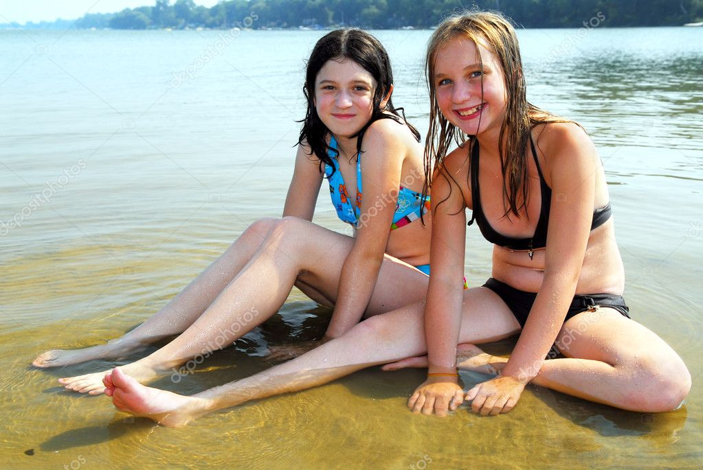 Two Preteen Girls Sitting In Shallow Water On A Beach 300 X 187.