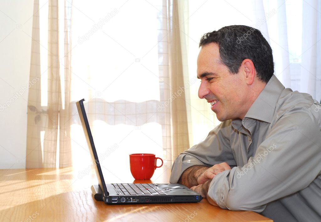 Man sitting at his desk with a laptop looking happy — Stock Photo #4953780