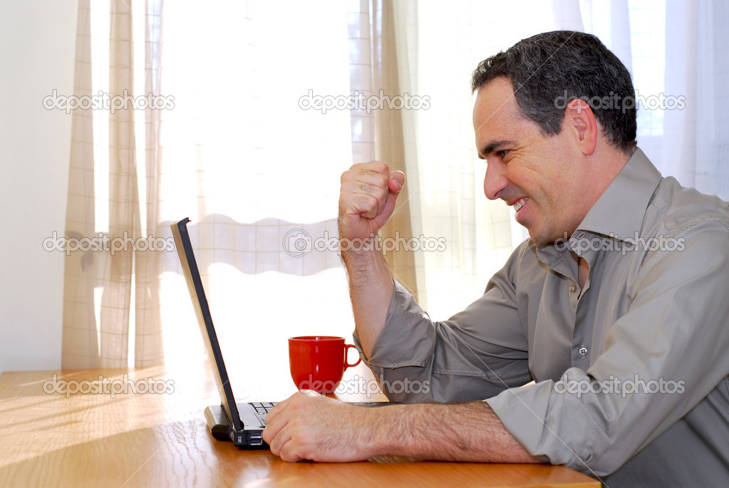 Man sitting at a desk and looking into his computer showing happiness and excitement — Stock Photo #4953799